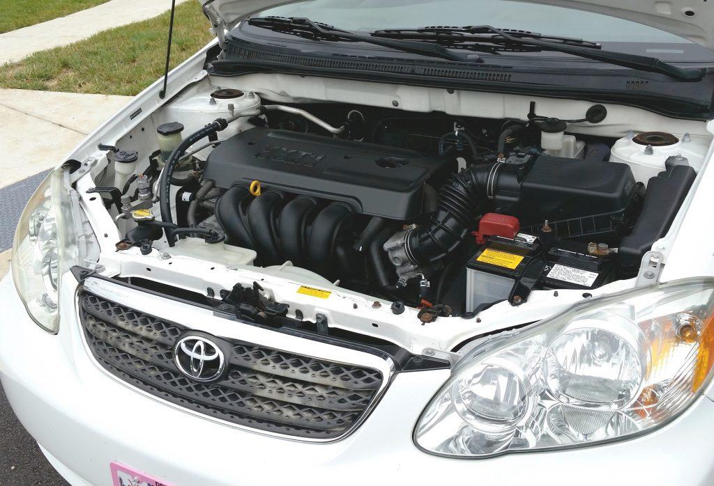 frente de um automóvel com o capô aberto e onde pode-se ver o motor e, mais a direita, a bateria.