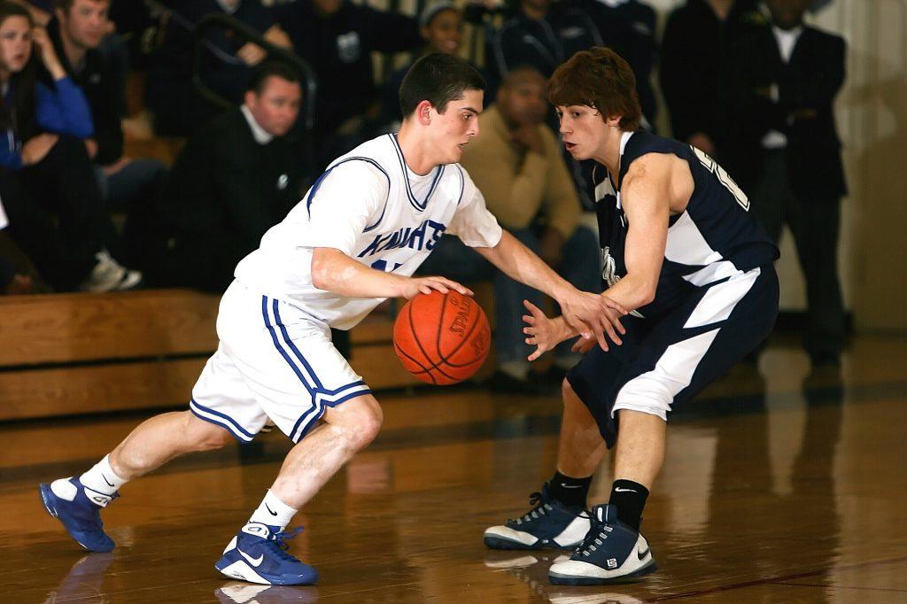 Dois garotos disputando a bola de basquete em quadra.