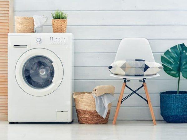 Na foto uma lavadora ao lado de um cesto de roupas, uma cadeira e um vaso de planta.