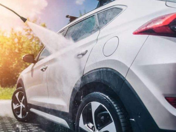Na foto uma mangueira de lavadora de alta pressão direcionada para um carro.