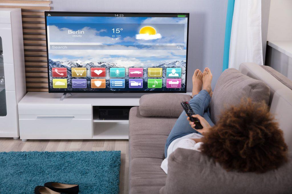Mulher deitada no sofá com controle na mão apontando para uma TV em um rack.