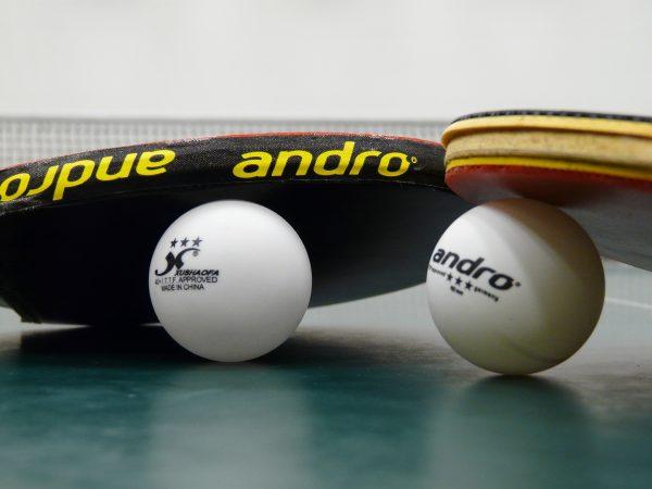 Imagem em zoom de duas raquetes de tênis de mesa apoiadas sobre duas bolinhas à frente de uma rede de tênis de mesa