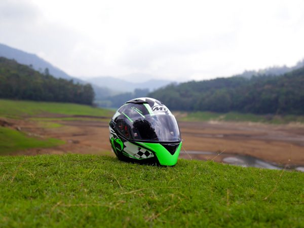 Um capacete para moto em cima de um gramado rodeado por árvores.
