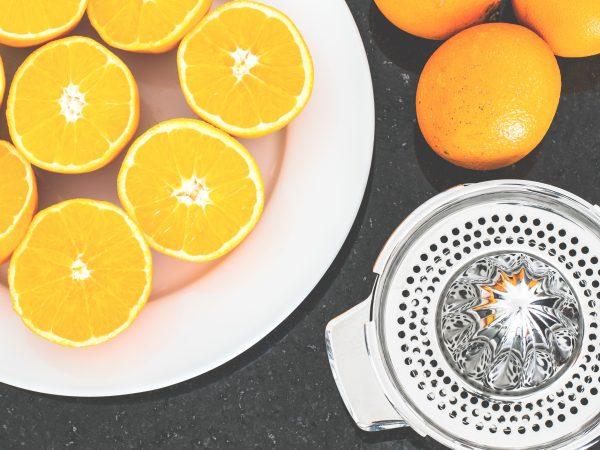 Imagem de extrator de suco ao lado de laranjas inteiras e outras cortadas ao meio sobre um prato branco