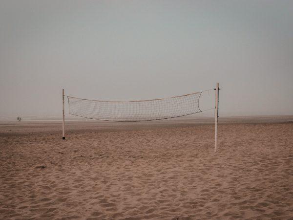 Imagem mostra uma rede de futevôlei centralizada, em meio à uma praia vazia.