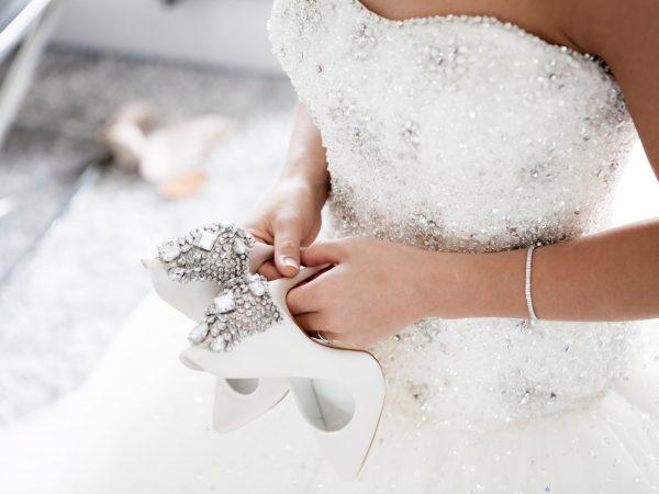 Na foto uma noiva segurando um par de sapatos.