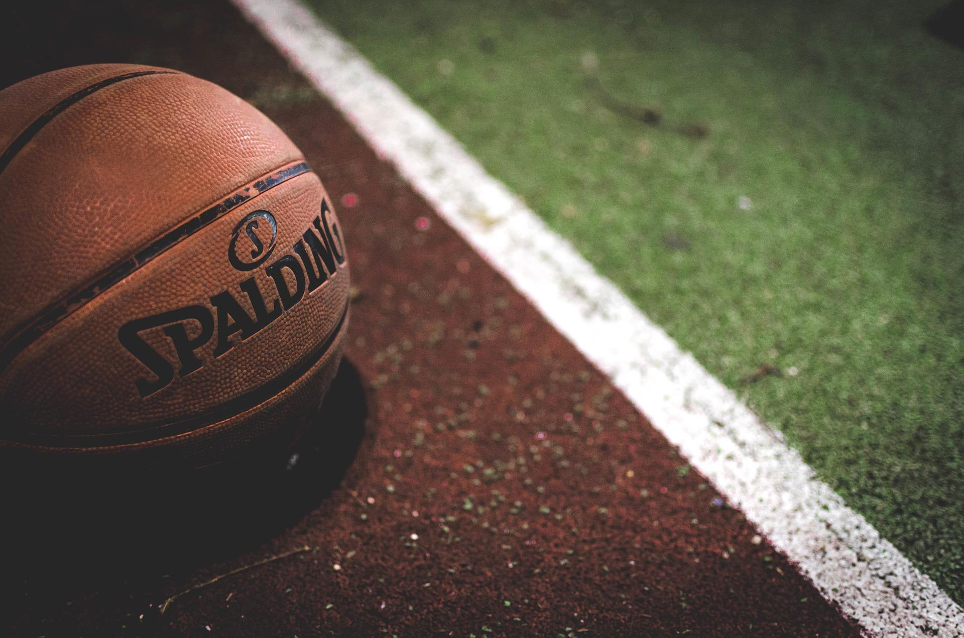 Imagem mostra o close de uma bola Spalding, com seu logo voltado para a câmera, sob o o chão de uma quadra, com as linhas bem demarcadas.