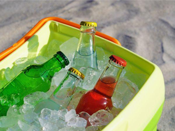 Imagem mostra um close de garrafas de vidro no topo de uma caixa térmica repleta de pedras de gelo.