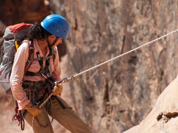 Imagem mostra uma pessoa usando cinto de segurança paraquedista enquanto pratica rapel.
