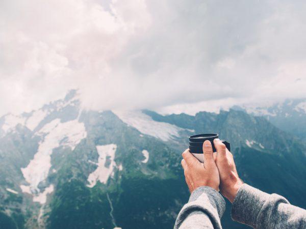 Na foto um homem segurando um copo em frente a algumas montanhas.
