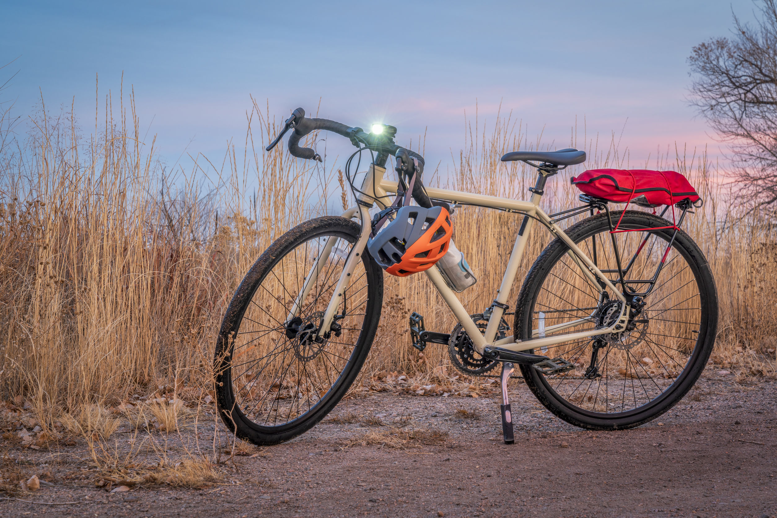 Imagem mostra uma bicicleta estacionada num campo aberto, com cascalhos no chão e mato alto ao fundo.