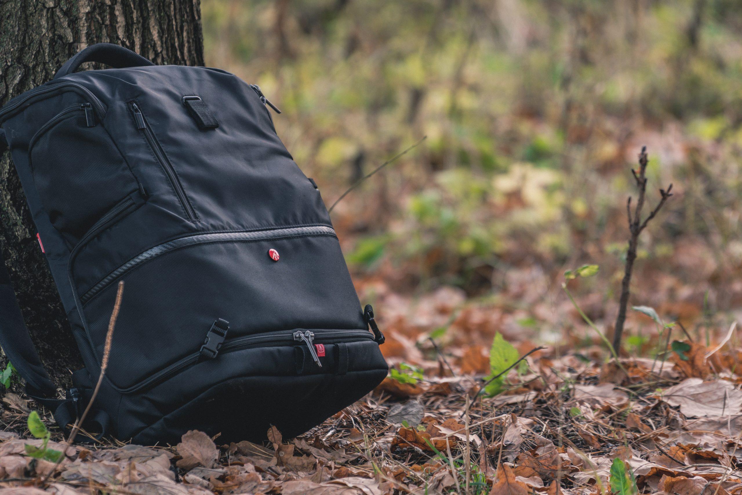 Na foto uma mochila preta no chão encostada em uma árvore.