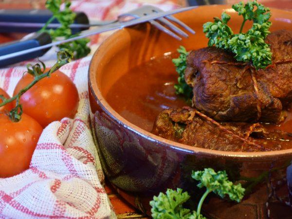 Imagem de panela de barro com ensopado com carne enrolada sobre a mesa, com tomates e talheres