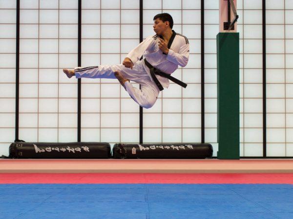 """Imagem mostra um homem treinando caratê, aplicando um chute no ar, """"voando"""" sobre o tapete."""