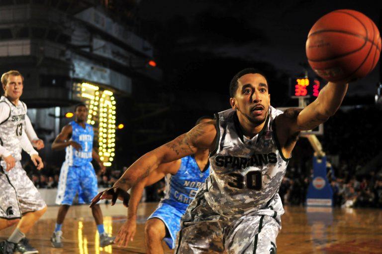 Imagem mostra o momento de um jogo de basquete, focando num jogador, com os braços esticados e olhos atentos, alcançando uma bola de basquete, que está no ar, na altura da sua cabeça.