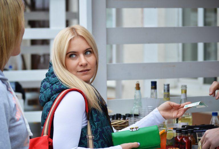 Imagem de uma mulher fazendo um pagamento enquanto segura uma carteira verde