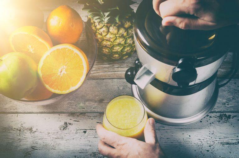 Imagem de laranjas cortadas ao lado de extrator de suco