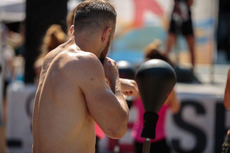 Imagem mostra uma lutadora dentro de um ringue, logo ao lado das cordas de um dos lados. Ela está com a guarda alta, e olha focada em algo fora do quadro.