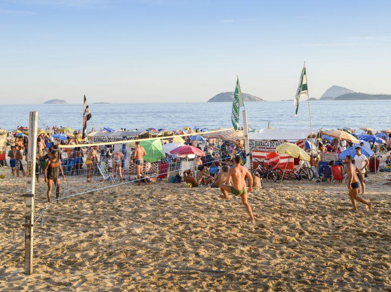 Imagem mostra pessoas jogando futevôlei em praia de Ipanema lotada