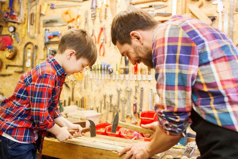 Imagem de um menino manuseando um martelo com a ajuda do pai.