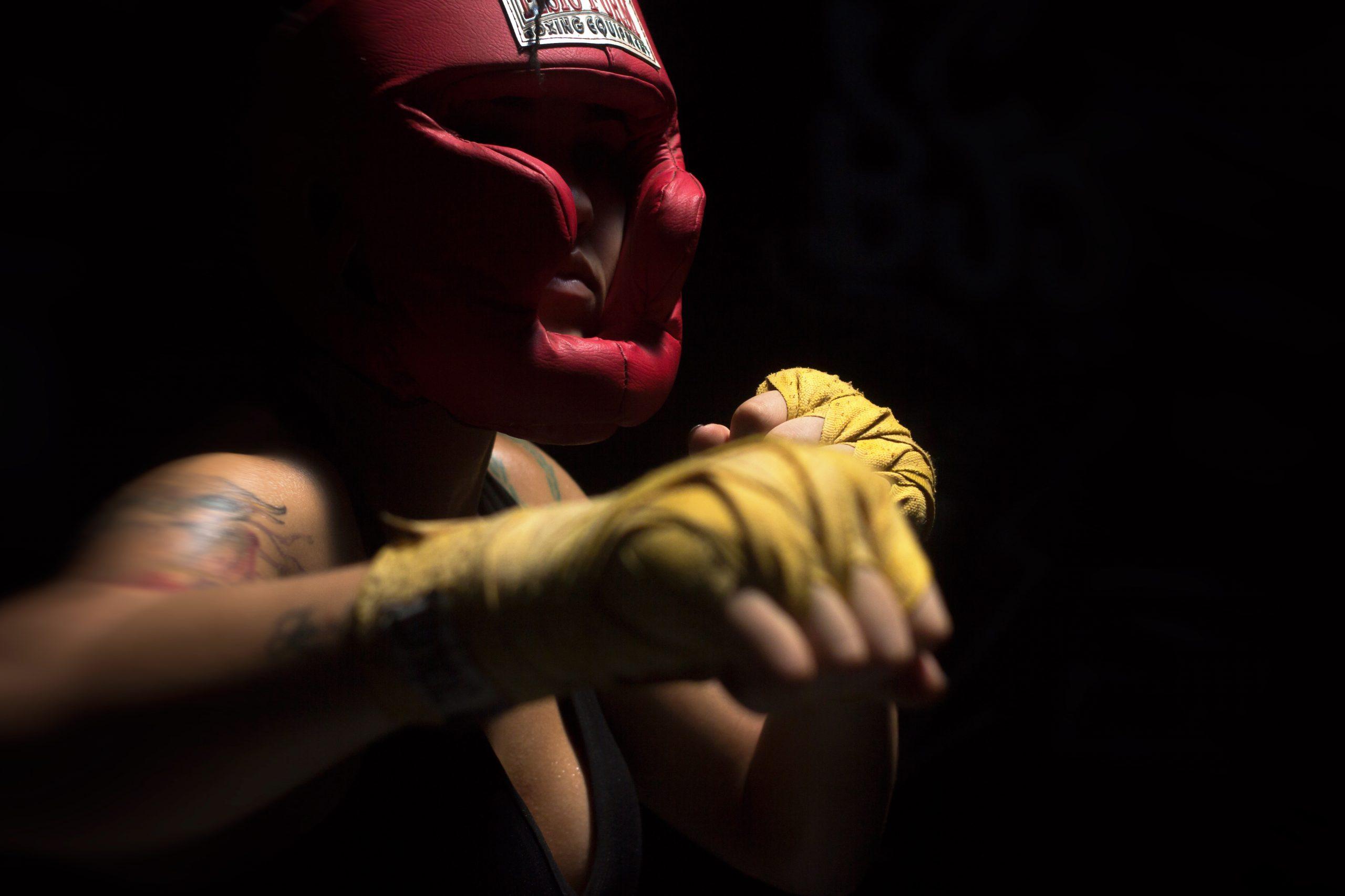 Imagem mostra uma lutadora de MMA de costas para a câmera, com os braços abertos, a caminho do ringue.