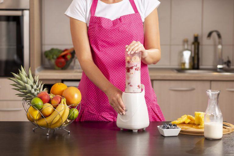 Mulher preparando vitamina em blender na bancada de cozinha.