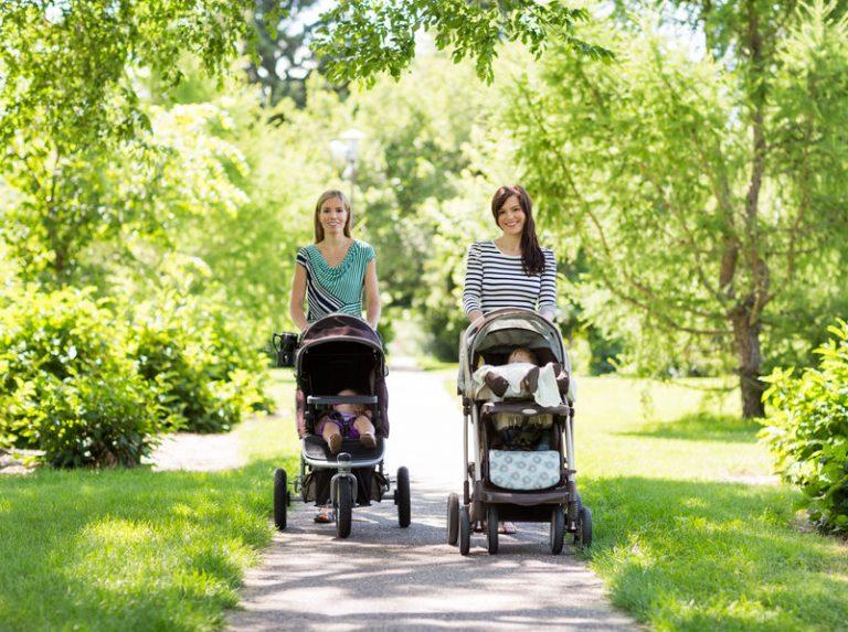 Duas mães passeando com seus bebês em seus carrinhos no parque.