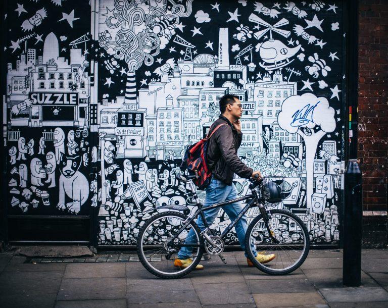 Imagem mostra um homem passando em frente a um muro grafitado, enquanto empurra sua bicicleta pela calçada.