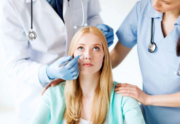 Médico e enfermeira examinando rosto de paciente.