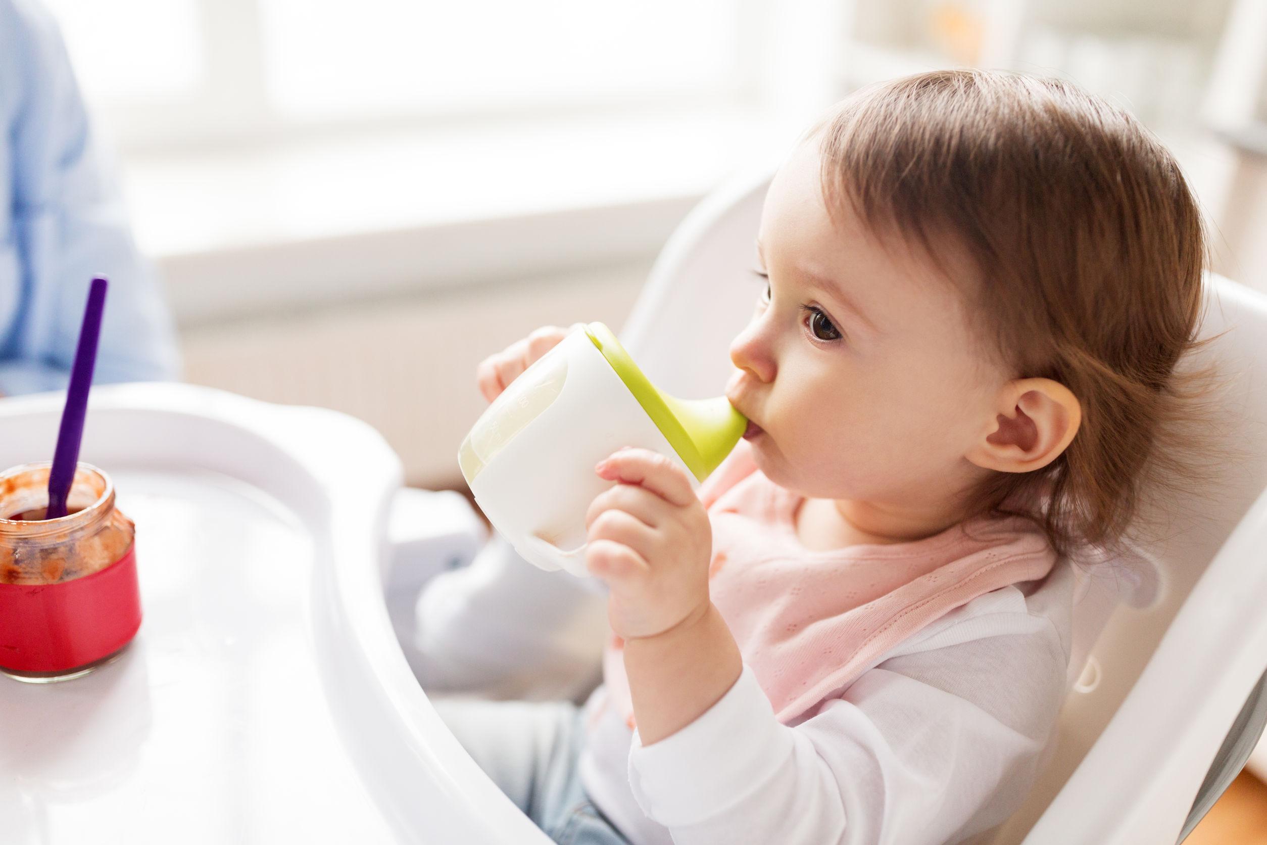 Bebê sentado em cadeirinha de alimentação bebendo em copo de transição