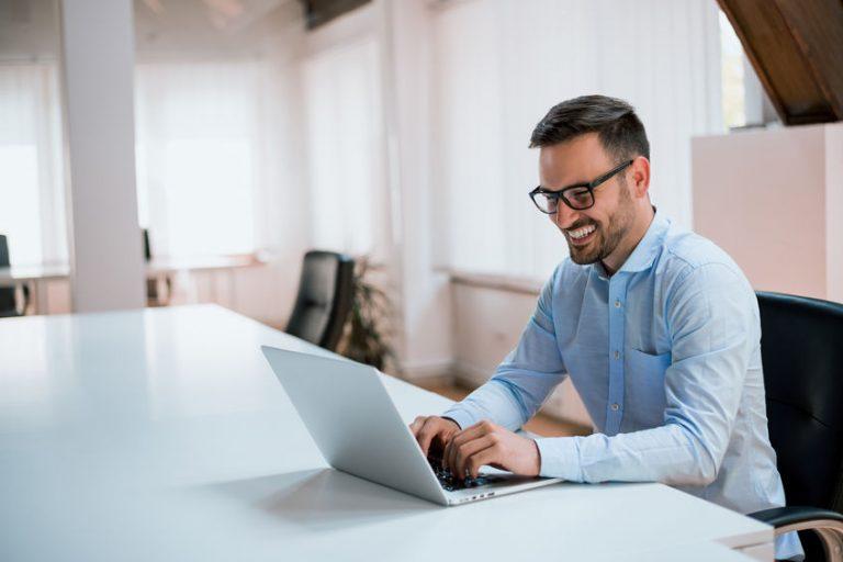 Homem sentado em mesa com notebook.