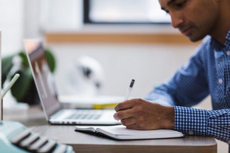 Rapaz fazendo anotações em caderno com o notebook aberto.