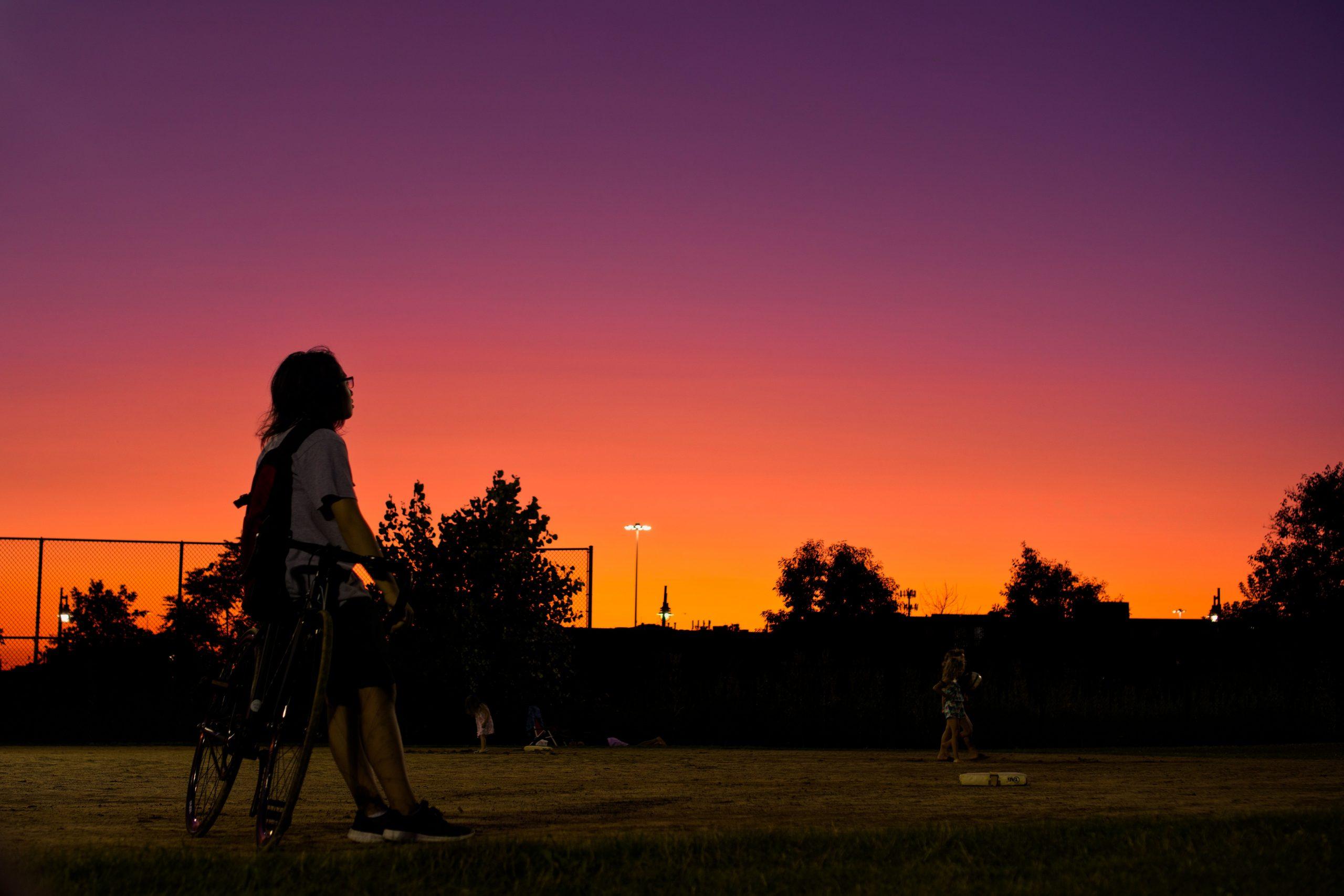 Imagem mostra um rapaz num campo de beisebol, apoiado em sua bike estacionada, admirando o pôr do sol.