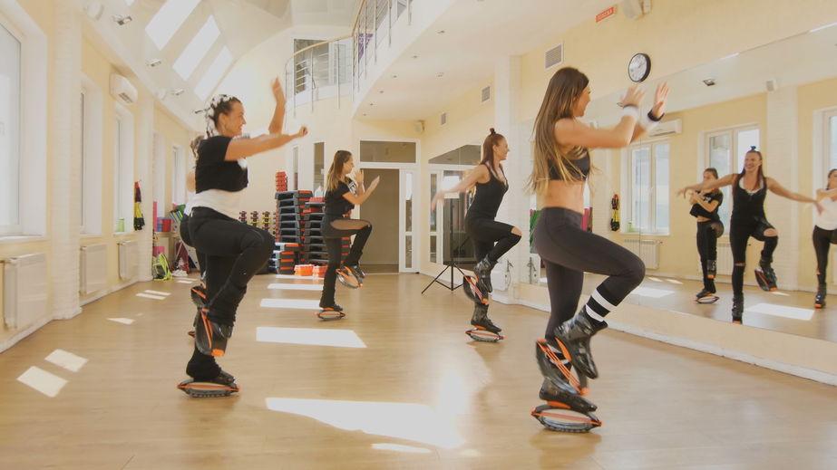 Imagem mostra um grupo de mulheres dançando em frente ao espelho de uma sala de uma academia, todas elas etão usando Kangoo Jumps.