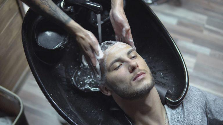 Imagem de cabelereiro lavando o cabelo do cliente em lavatório portátil