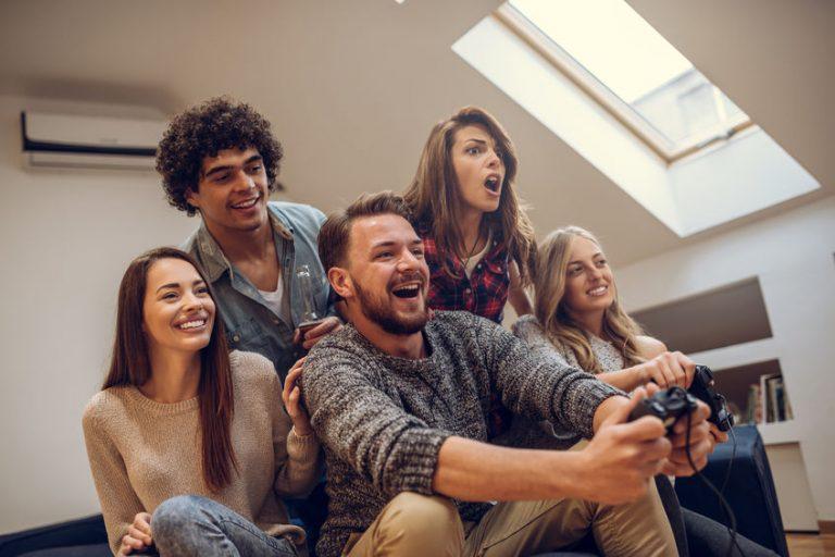 Imagem mostra um grupo de cinco amigos se divertindo com um videogame. Dois deles jogam, e outros três reagem ao game, que está fora do quadro retratado.