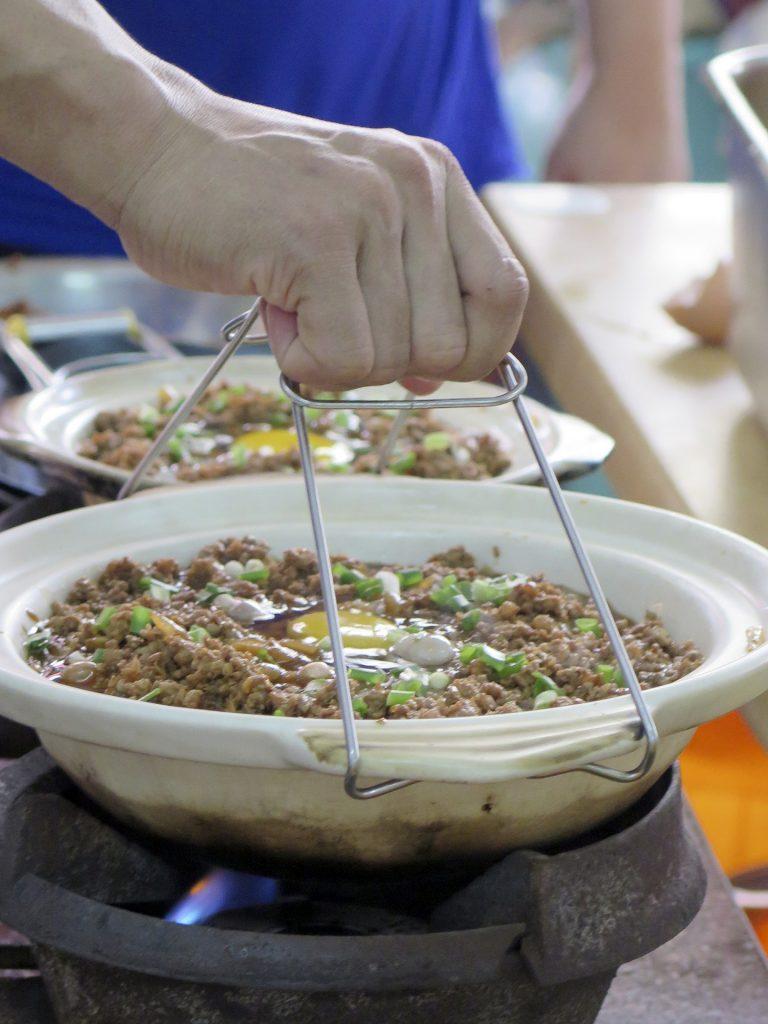 Imagem de pessoa segurando uma panela de barro com comida asiática sobre um fogareiro