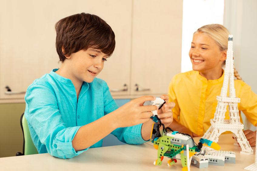 Menino e menina montando escultura em 3D.