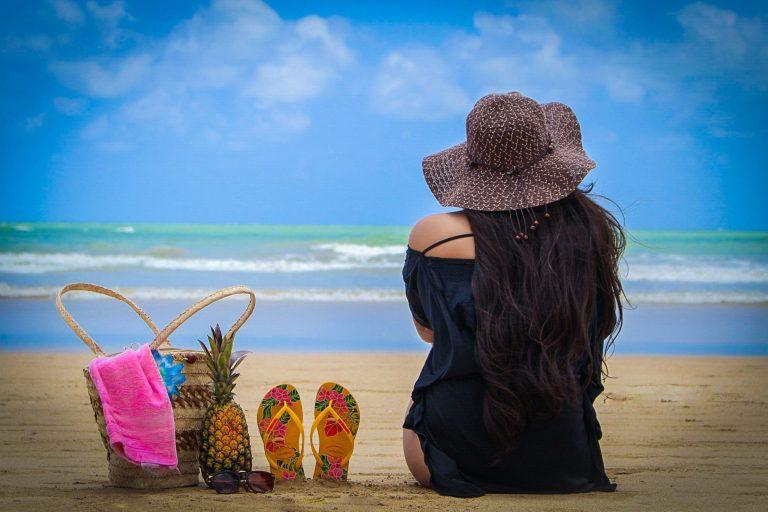 Mulher sentada na areia da praia com chinelos, bolsa e um abacaxi ao lado.