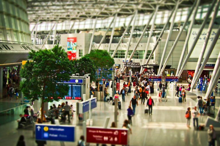 Terminal de aeroporto com passageiros caminhando.
