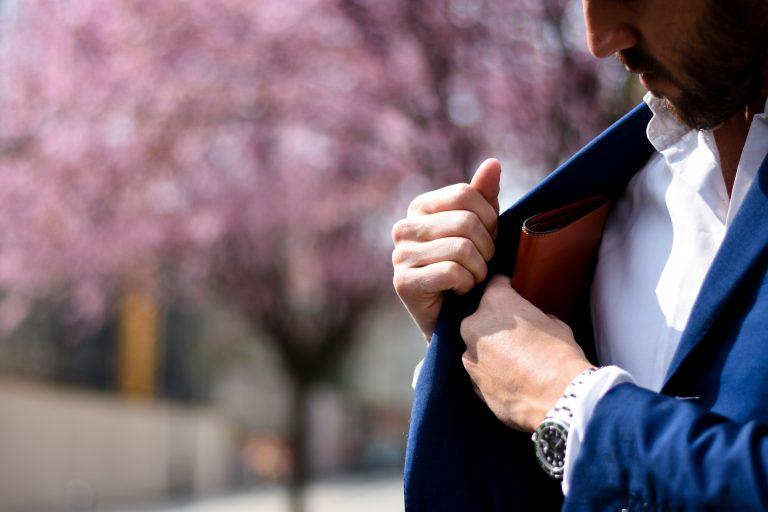 Imagem de um homem colocando uma carteira slim no bolso interno do paletó