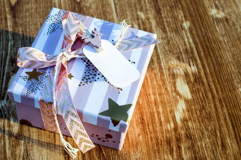 Na foto uma caixa de presente listrada com estrelas.