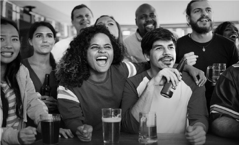 Imagem mostra uma turma de amigos num bar, acompanhando um jogo. Há uma mulher, ao centro, que comemora efusivamente, com o braço esquerdo apoiado sobre um rapaz ao seu lado, com uma garrafa de cerveja na mão.
