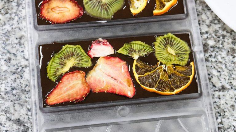 Imagem de barras de chocolate com morangos, laranjas e kiwis desidratados