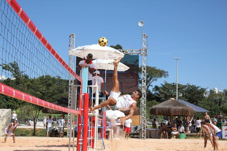 Imagem mostra um atleta atacando a bola com a sola do pé, como uma bicicleta do futebol, só que frontal. Ele atua numa competição, sob os olhos do juíz e com outro jogo sendo disputado ao fundo.