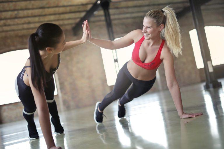 Na foto duas mulheres fazendo exercícios.