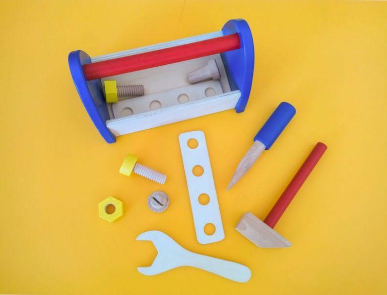 Maleta e ferramentas de brinquedo sobre bancada.