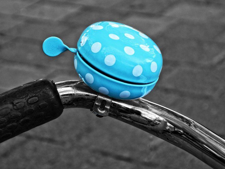 Imagem aproxiamda de buzina de bicicleta azul com bolas brancas