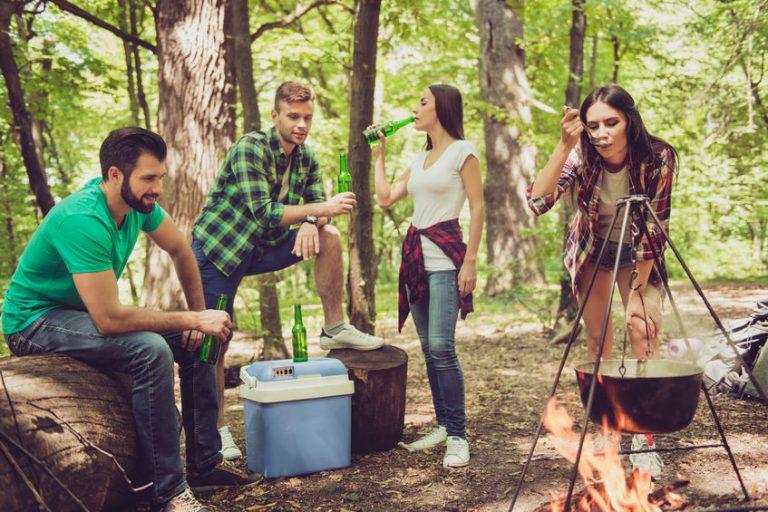 Imagem mostra quatro amigos acampando. Três deles tomam cervejas ao redor de uma caixa térmica pequena, enquanto a quarta cuida de uma panela de sopa sobre a fogueira.