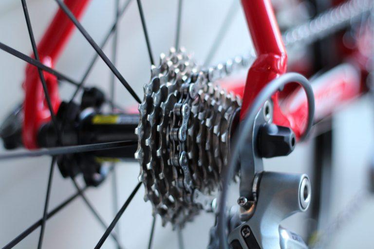 Imagem mostra o close dos dentes de uma catraca instalada numa roda de bicicleta, cujos aros e outras engrenagens estão fora de foco.